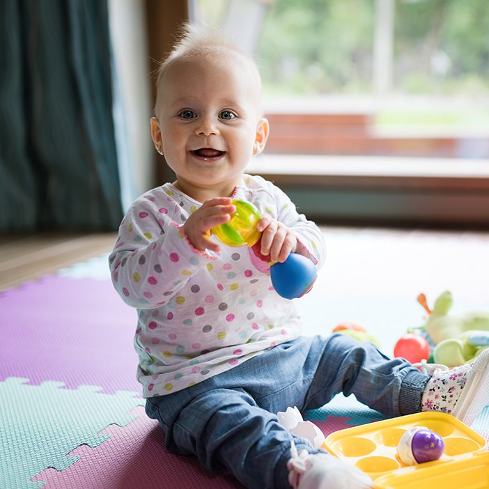 Baby toddler girl playing color toys at home or nursery
